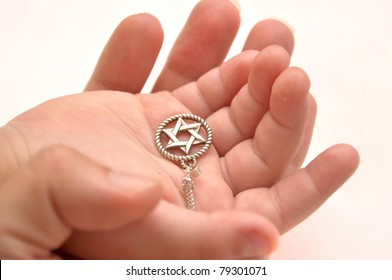 Mother and child's hands holding silver star of David