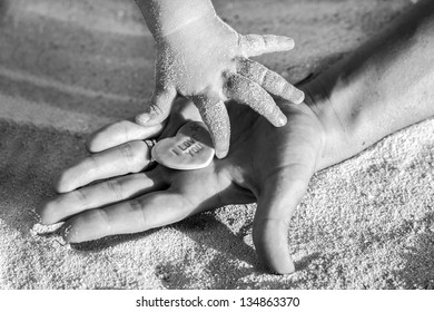 Mother and child's hands on the beach in  the Caribbean part of Mexico, Riviera Maya. Summer beach background.