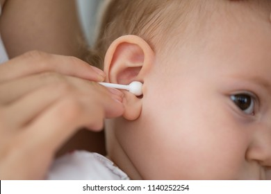 mother cleaning babies ear with cotton swabs