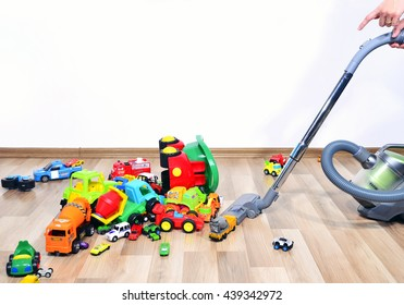 Mother cleaning the messy room full of toys. Close up on woman's hands cleaning with a vacuum cleaner. Lots of toys, many cars piled on the floor