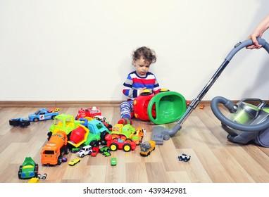 Mother cleaning the messy room full of toys. Close up on woman's hands cleaning with a vacuum cleaner. Upset kid playing with many toys on the floor