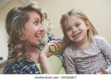 Mother combing daughter's  hair.