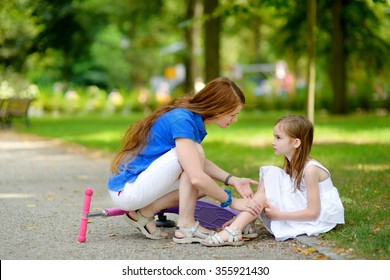 Mother comforting her daughter after she fell while riding her scooter at summer park