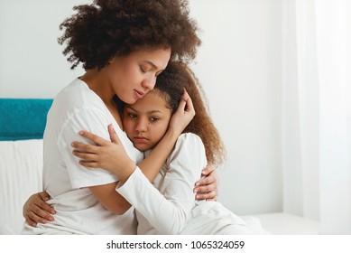 Mãe confortando sua filha, sentado no quarto, abraçando