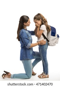 Mother comforting her sad daughter that is crying on the first day of school