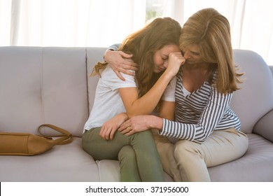 Mother comforting her teenage daughter at home on the couch