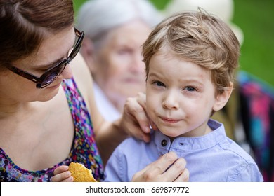 Mother comforting son after falling down and hurting face during walk in park. Boy eating cookie, senior grandmother sitting beside on bench.