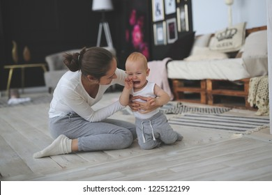Mother comforts a crying baby on the floor in a bright room. The concept of motherhood, adoption.