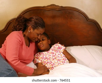 A mother comforts her sick daughter.