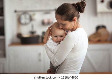 mother comforts a sad baby, mom holds her son in her arms in a real bright interior.