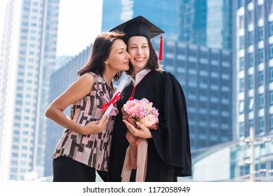 Mother congratulations, kiss, give flower to daughter. Two girls hug and congratulations each other at the university. They are graduates and hold diploma certificate. They are happy and in good mood.