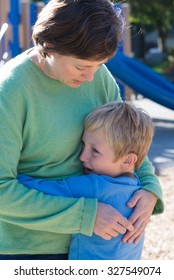A mother consoles her son, perhaps over a playground altercation.