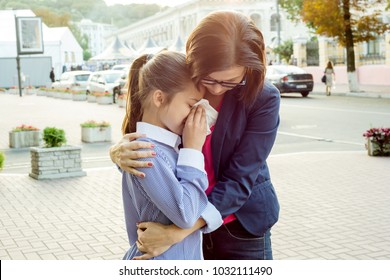 Mother consoling her crying daughter. Urban background