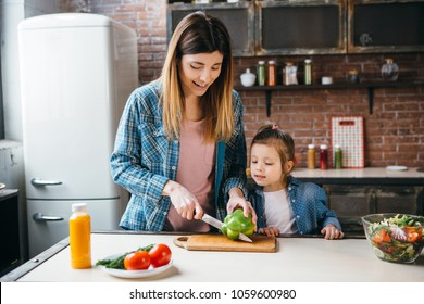 Mother cook with daughter on kitchen,cut green pepper.