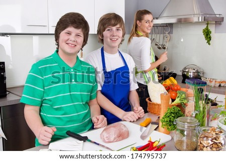 Mother cooking with her sons in the kitchen - family life.