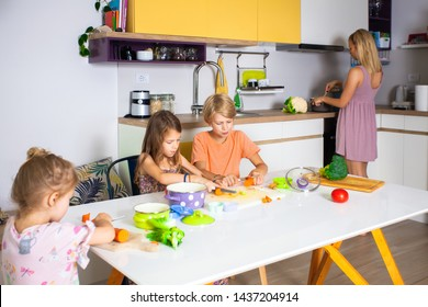 Mother is cooking while children helping and cutting different types of vegetables .Happy and healthy life concept