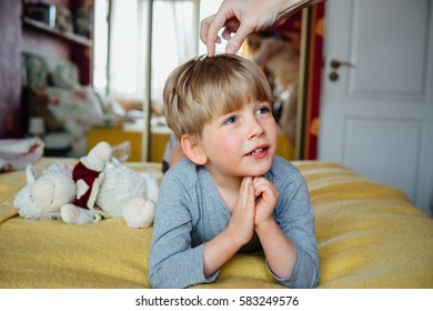 Mother corrects the child's hair. Cute handsome  boy (5 years)  lying on the  bed.