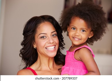 Mother Cuddling Daughter At Home