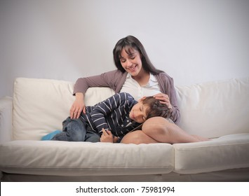 Mother cuddling her child on a sofa