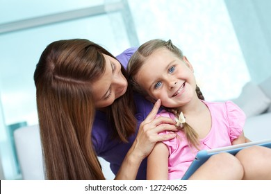 Mother cuddling her daughter while she looking at camera at home