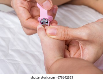 Mother cut nail foot her baby with pink nail cilpper.