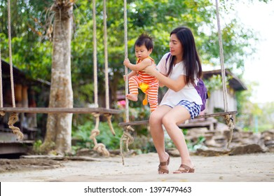 Mother and cute baby child outdoors on tree swing smiling,family love,   Mother and mischievous child.