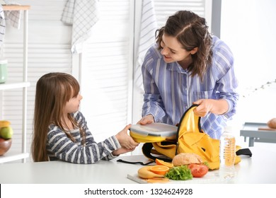 Mother with cute daughter packing lunch box into backpack at home