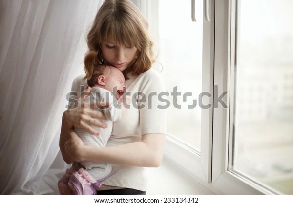 かわいい子どもの泣く赤ちゃんを持つ母親