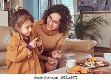 Mother with cute little daughter having breakfast on the sofa at home.