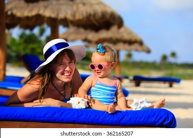 mother and cute little daughter having fun on beach