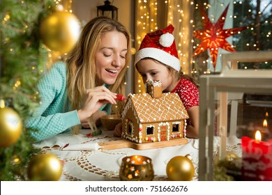 Mother and cute little girl in red hat decorating gingerbread house. Beautiful living room with lights and Christmas tree, table with candles and lanterns. Happy family celebrating holiday together.