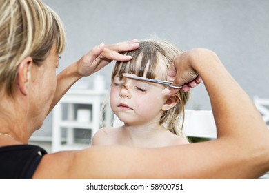 Mother cutting daughters hair outdoor