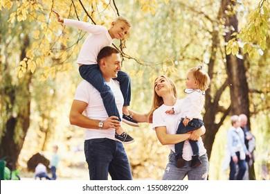 Mutter und Vater halten Kinder in Schultern und Händen. Freuen Sie sich auf einen Spaziergang in einem Herbstpark.