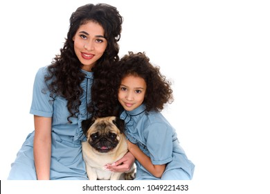 c11dfe70e973 mother and daughter with adorable pug looking at camera isolated on white