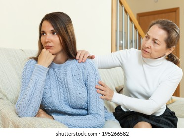 Mother and daughter after quarrel on sofa  in home interior