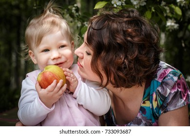 Mother and daughter with apple in the hand in the park