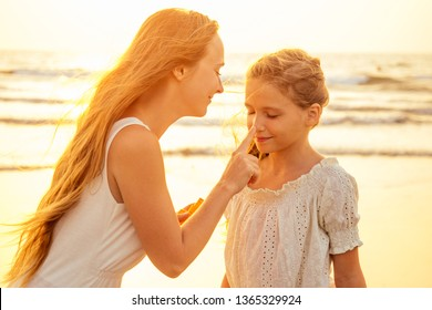 Mother and daughter applying sunscreen on body spf