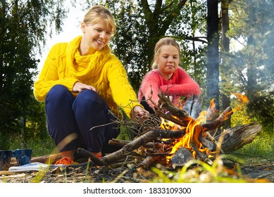mother and daughter in the autumn forest sitting by the fire. mom and daughter making fire in woods.