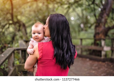 Mother and daughter baby in summer meadow park