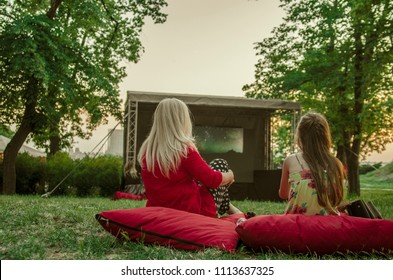 Mother and daughter back,sitting on pillows on green grass in open cinema and watching movie.Entertainment in nature