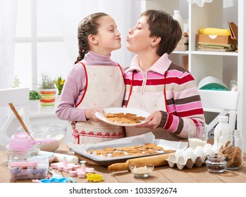 Mother and daughter baking cookies, home kitchen interior, healthy food concept