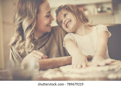 Mother and daughter baking cookies. Looking at each other.
