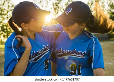 A mother and daughter baseball players together on the playground
