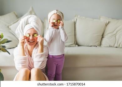 mère avec sa fille en peignoir de bain avec une serviette sur la tête prend soin de la peau à la maison, des concombres aux yeux, des soins à domicile