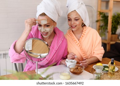 Mother and daughter in bathrobes and towels on head using natural cosmetics