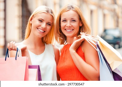 Mother and daughter are the best friends. Beautiful mature woman and her blond hair daughter holding shopping bags and looking at camera while standing outdoors