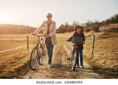 Mother and daughter with bicycles on countryside.