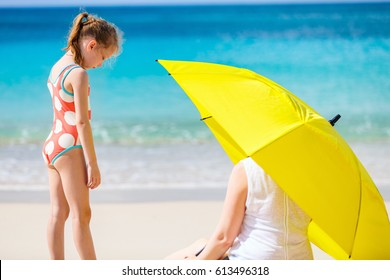 Mother and daughter with big yellow umbrella hiding from sun at tropical beach