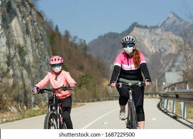 Mutter und Tochter, die mit dem Rad fahren und medizinische Maske gegen das Korona-Virus tragen
