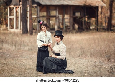 Mother and daughter in a black top hat and white shirt posing outdoors